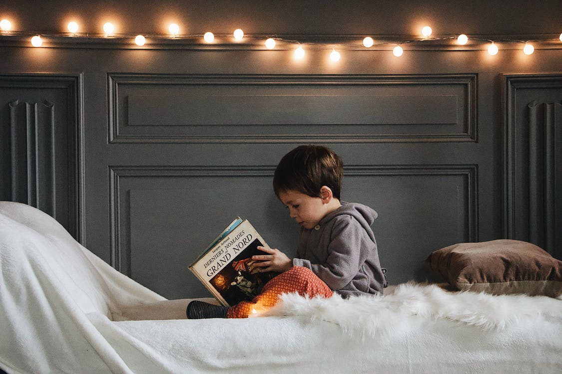 A kid reading in a corner